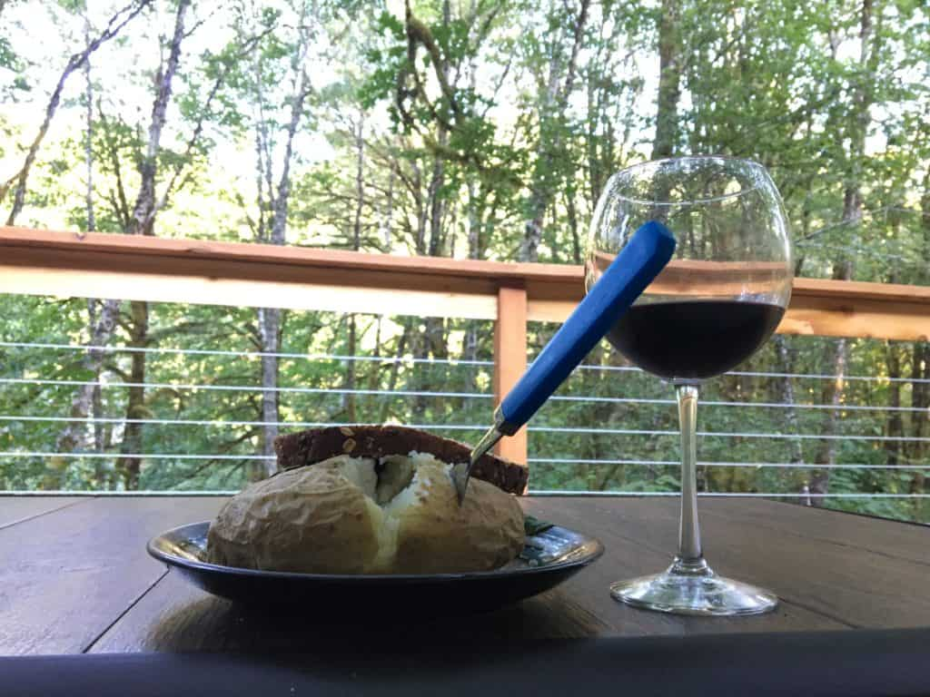 There's a very tasty veggie burger behind that tasty potato, both heated in the microwave. Plus, wine.